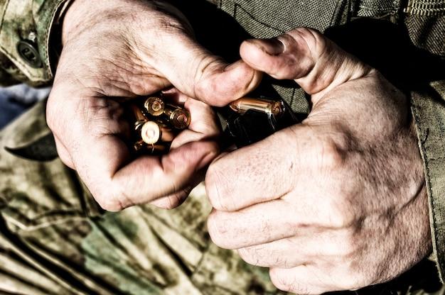 De jager bereidt een clip met kogels voor voor het volgende gevecht. gemengde media