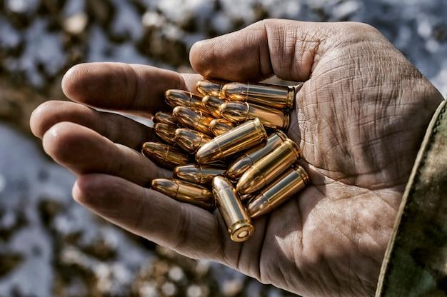 De jager houdt een handvol kogels in zijn handpalm als wapens.