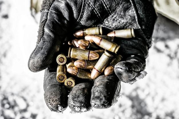 De jager houdt een handvol kogels in zijn handpalm als wapens. Premium Foto