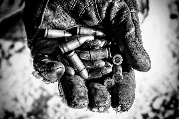 De jager houdt een handvol kogels in zijn handpalm voor wapens. gemengde media
