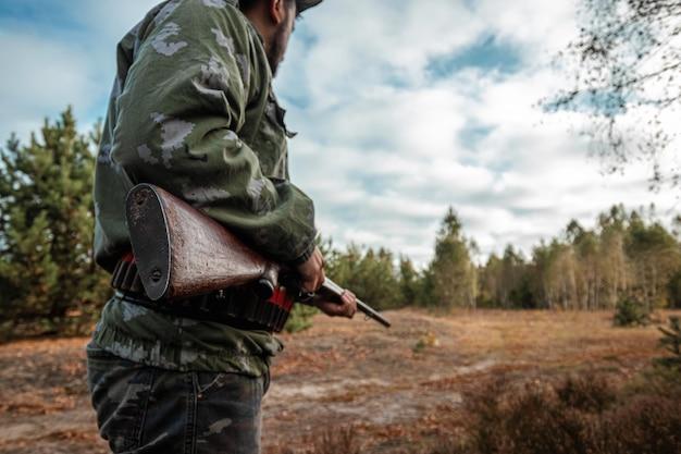 De jager met een pistool in zijn handen jaagt kleding in het herfstbos