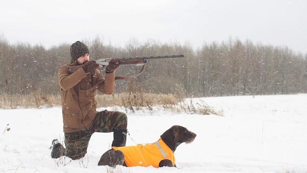 De jager richt op de vogel en de hond wacht op het schot. hobby jagen