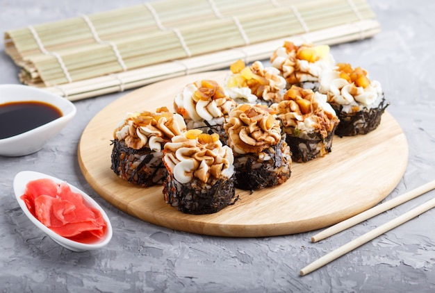 De japanse broodjes van makisushi met roomkaas op houten raad op grijs beton