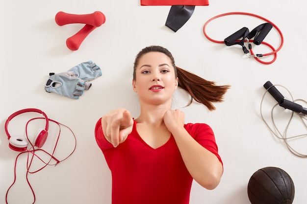 De jonge aanbiddelijke punten van de vrouwenholding bij camera met haar wijsvinger terwijl het leggen op witte oppervlakte, kleedt het meisje met paardestaart rode kleding
