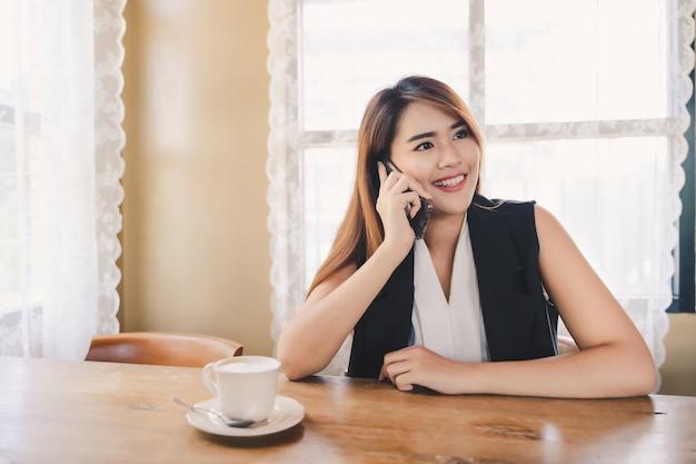 De jonge aantrekkelijke aziatische bedrijfsvrouw roept of gebruikt smartphone in koffie