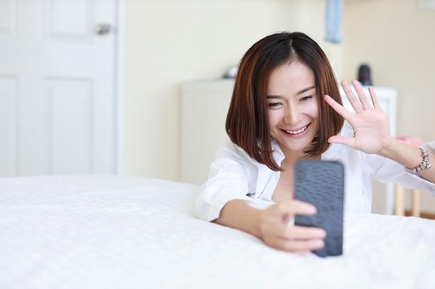 De jonge aantrekkelijke aziatische vrouw die wit overhemd dragen die vdo gebruiken roept van celtelefoon en zegt hallo tegen iemand terwijl het zitten in slaapkamer