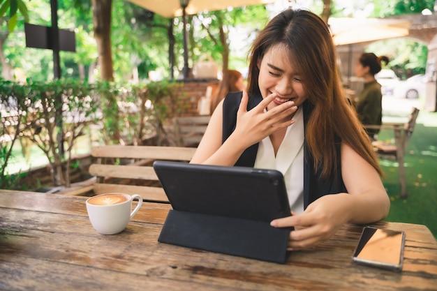 De jonge aantrekkelijke aziatische vrouw in gelukkig voelen gebruikt tablet in de winkel van de koffiekoffie