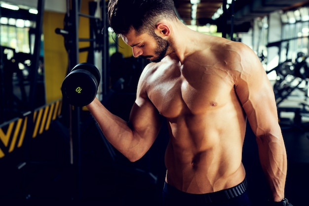 De jonge aantrekkelijke bodybuilder werkt met domoren uit.