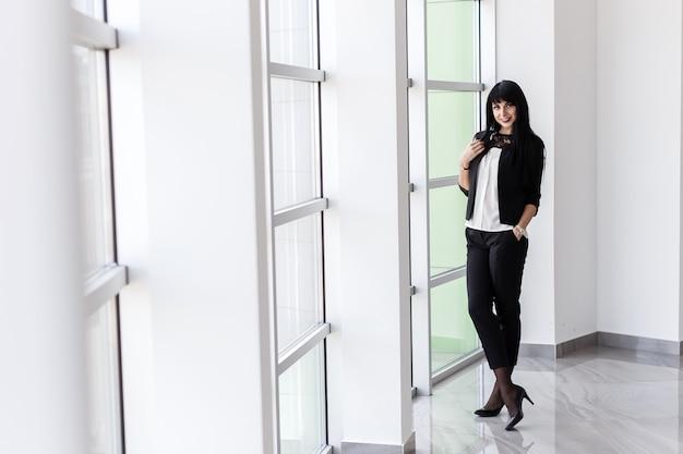 De jonge aantrekkelijke gelukkige donkerbruine vrouw kleedde zich in een zwart pak die zich dichtbij het venster in bureau, het glimlachen bevinden, die camera bekijken.