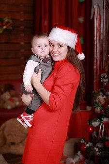 De jonge aantrekkelijke gelukkige moeder in de hoed van santa heeft een goede tijd met haar zoon thuis dichtbij kerstboom. familie, geluk, vakantie, nieuwjaarsconcept