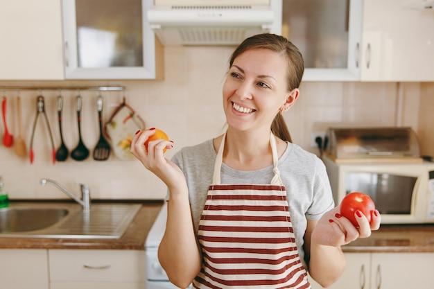 De jonge aantrekkelijke gelukkige vrouw in een schort besluit een rode of gele tomaat in de keuken te kiezen. dieet concept. gezonde levensstijl. thuis koken. eten koken.