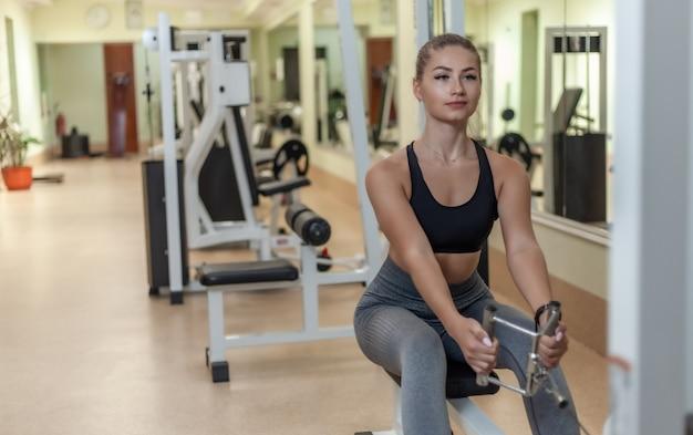 De jonge aantrekkelijke geschikte vrouw leidt in oefeningsmachine op in de gymnastiek. verticale tractie