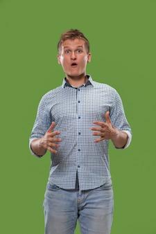 De jonge aantrekkelijke man die verrast kijkt die op groen wordt geïsoleerd