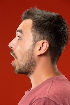 De jonge aantrekkelijke man die verrast kijkt die op rood wordt geïsoleerd