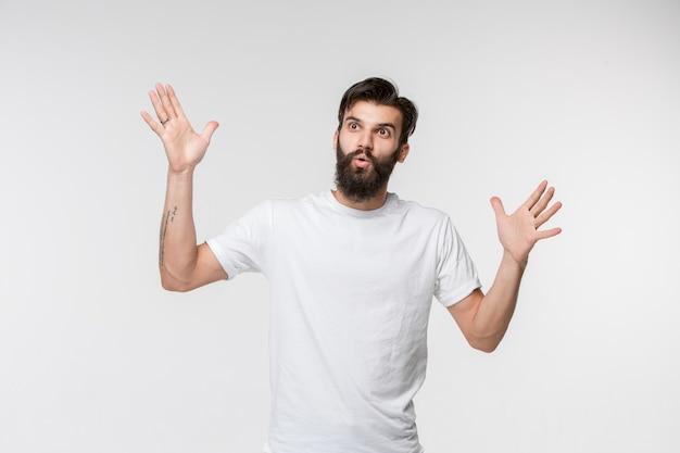 De jonge aantrekkelijke man die verrast kijkt die op wit wordt geïsoleerd