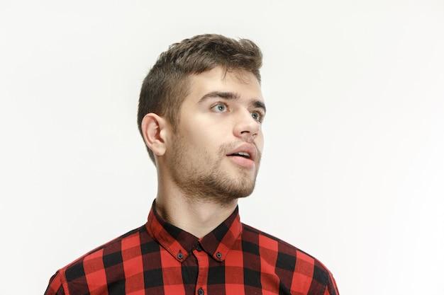 De jonge aantrekkelijke man die verrast kijkt