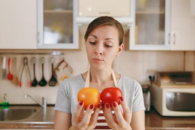 De jonge aantrekkelijke peinzende vrouw in een schort besluit een rode of gele tomaat in de keuken te kiezen. dieet concept. gezonde levensstijl. thuis koken. eten koken.
