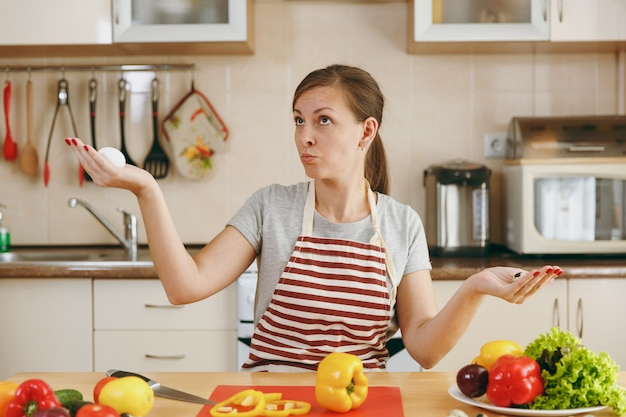 De jonge aantrekkelijke peinzende vrouw in een schort kiest tussen kip en kwarteleitjes in de keuken. dieet concept. gezonde levensstijl. thuis koken. eten koken.