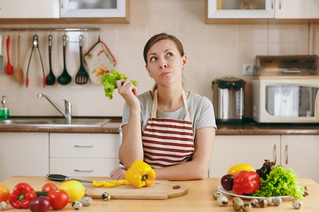 De jonge aantrekkelijke peinzende vrouw in een schort met slablad in de keuken. dieet concept. gezonde levensstijl. thuis koken. eten koken.