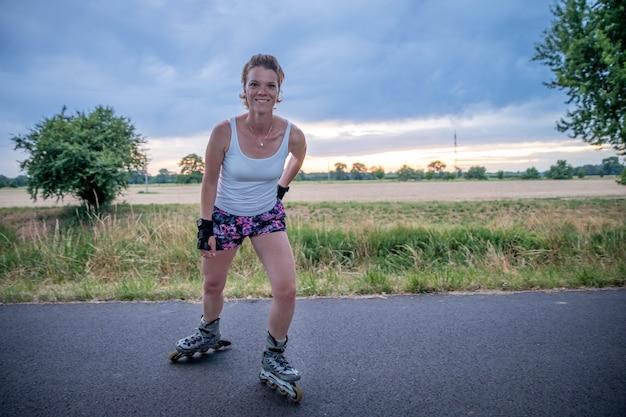De jonge aantrekkelijke vrouw berijdt rolschaatsen op het platteland in de zomer