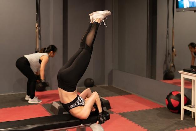 De jonge aantrekkelijke vrouw die abs training het doen van liftenbeen opheffen opheft of opwinding schopt oefening