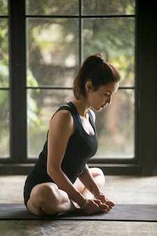 De jonge aantrekkelijke vrouw in baddhakonasana stelt