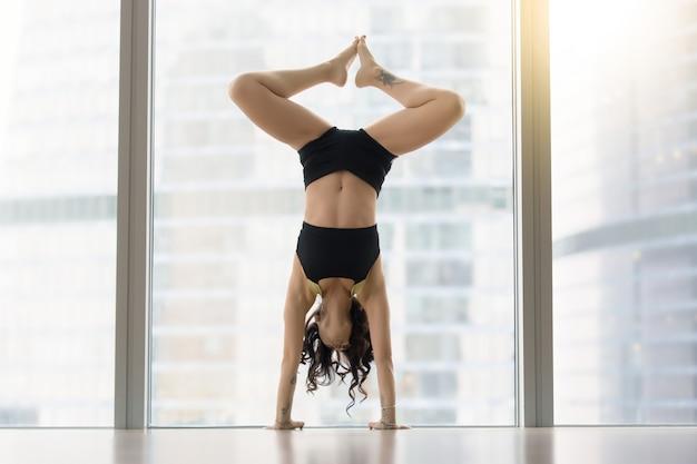 De jonge aantrekkelijke vrouw in dans stelt dichtbij vloervenster, handstan