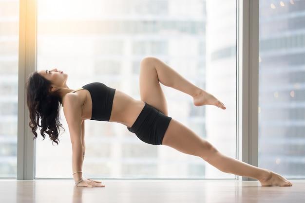 De jonge aantrekkelijke vrouw in stijgende plank stelt tegen vloervenster
