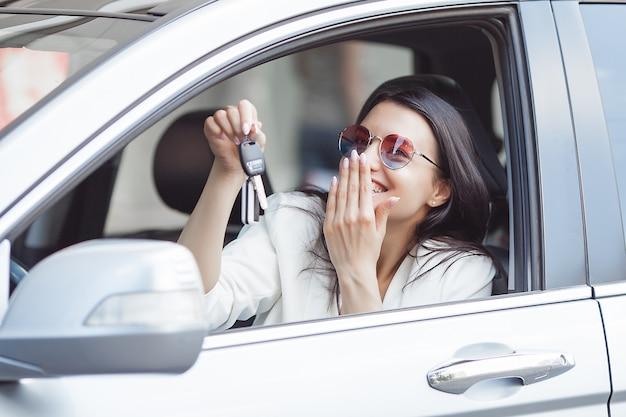De jonge aantrekkelijke vrouw kocht zojuist een nieuwe auto. vrouwelijke sleutels houden van nieuwe auto.