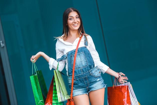 De jonge aantrekkelijke vrouw met het winkelen doet in openlucht in zakken