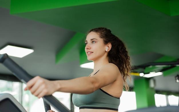 De jonge aantrekkelijke vrouw oefent op elliptische oefening machine in de gymnastiek. fitness, gezonde levensstijl concept.