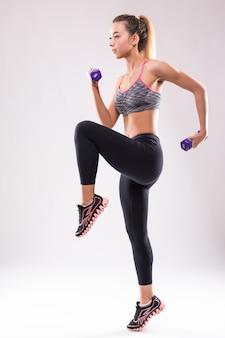 De jonge aantrekkelijke vrouw van het geschiktheidsmeisje maakt verschillende aerobicsoefeningen met domoren op wit