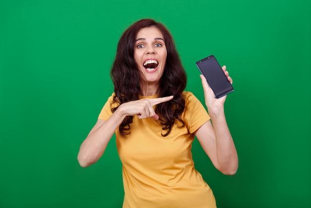 De jonge aantrekkelijke vrouw wijst op het lege scherm van telefoon in haar hand en onderzoekt een camera