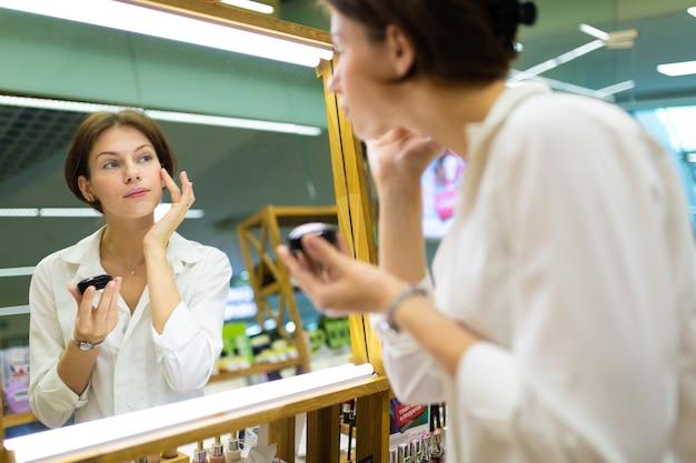De jonge aantrekkelijke vrouw zet op maakt omhoog bij skincaredenad omhoog opslag maakt