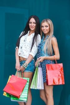 De jonge aantrekkelijke vrouwen met het winkelen doet in openlucht in zakken