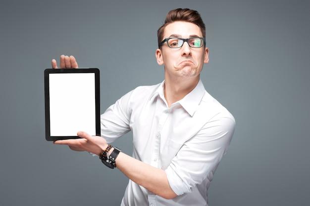 De jonge aantrekkelijke zakenman in duur horloge, zwarte glazen en wit overhemd houdt lege tablet