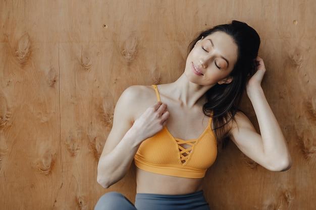 De jonge aantrekkelijke zitting van het geschiktheidsmeisje op de vloer dichtbij het venster op de oppervlakte van een houten muur, die op yogalessen rusten