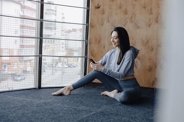 De jonge aantrekkelijke zitting van het geschiktheidsmeisje op de vloer, rustend op yogaklassen en sprekend op telefoon
