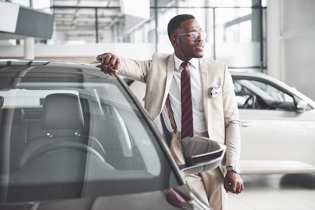 De jonge aantrekkelijke zwarte zakenman koopt een nieuwe auto, dromen komen uit.