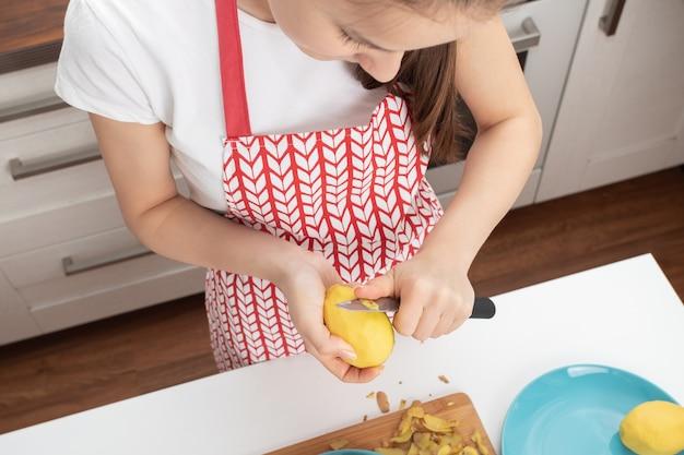 De jonge aardappels van de meisjesschil in de keuken