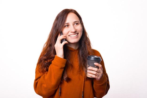 De jonge aardige vrouw praat met haar telefoon en houdt een kop heet water vast en kijkt weg en glimlacht