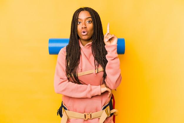 De jonge afrikaanse amerikaanse backpackervrouw isoleerde het hebben van één of ander groot idee, concept creativiteit.
