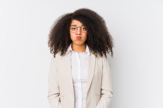 De jonge afrikaanse amerikaanse bedrijfsvrouw blaast wangen, heeft uitdrukking vermoeid. gelaatsuitdrukking concept.