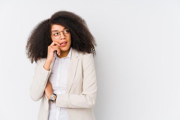 De jonge afrikaanse amerikaanse bedrijfsvrouw ontspande het denken over iets bekijkend een exemplaarruimte.