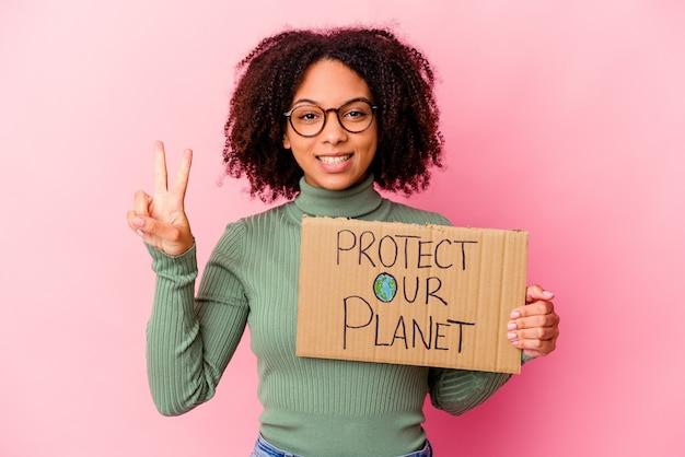 De jonge afrikaanse amerikaanse gemengde rasvrouw die houdt beschermt ons planeetkarton dat nummer twee met vingers toont.