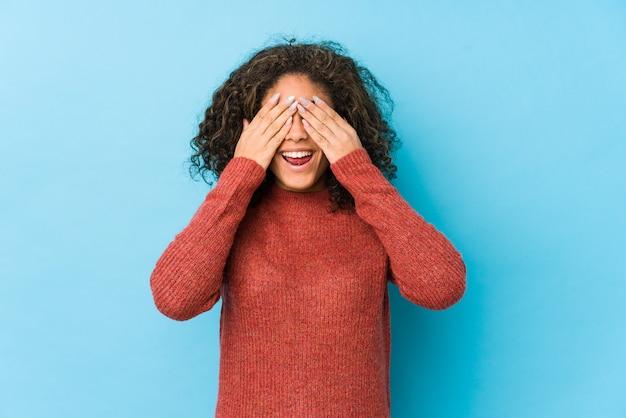De jonge afrikaanse amerikaanse krullende haarvrouw behandelt ogen met handen, glimlacht breed wachtend op een verrassing.