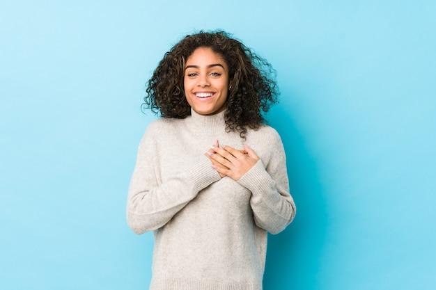 De jonge afrikaanse amerikaanse krullende haarvrouw heeft vriendschappelijke uitdrukking, drukkend palm aan borst. liefde concept.