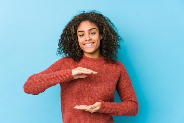 De jonge afrikaanse amerikaanse krullende holding van de haarvrouw iets met beide handen, productpresentatie.