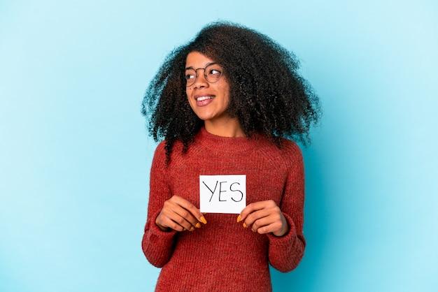 De jonge afrikaanse amerikaanse krullende vrouw die een ja aanplakbiljet houdt kijkt opzij glimlachend, vrolijk en aangenaam.