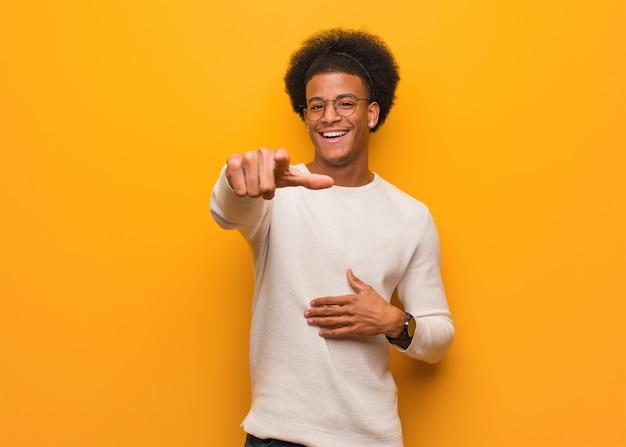 De jonge afrikaanse amerikaanse mens over een oranje muur droomt van het bereiken van doelen en doeleinden